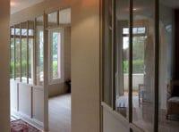 verrière structure bois entre une entrée et le salon d'une maison